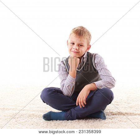 Beautiful Teenager Looking At Camera And Smiling While Sitting On The Floor On A White Background