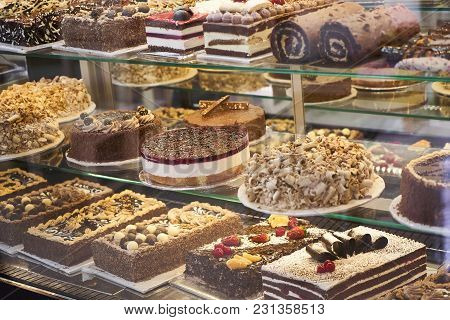 Different Types Of Cakes In Pastry Shop Glass Display, Showcase With Sweets Cakes, Pastries, Biscuit
