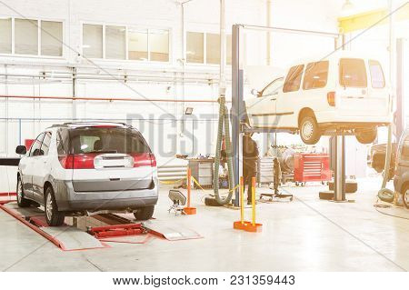 Car Service Center. Vehicle Raised On Lift At Maintenance Station. Auomobile Repair And Check Up.