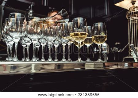 Served Table At Wine Tasting. Bartender Pouring White Wine From A Decanter Into Glasses
