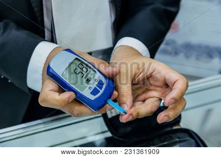 Man Measuring Glucose Level In Blood By Using Digital Glucometer.
