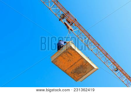 Male In Bucket Of Tower Crane. Building Construction Site. Blue Sky Background