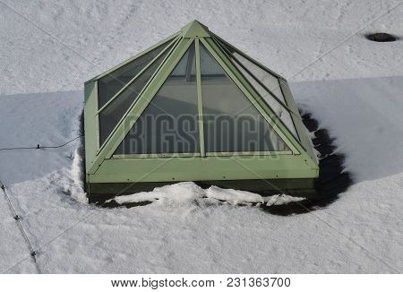 Pyramid Shaped Glass Skylight Window On A Snow-covered Roof.