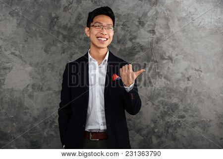 Portrait of a happy young asian man dressed in suit pointing finger away at copy space over gray background