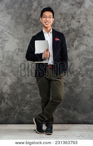 Full length portrait of a cheerful young asian man dressed in suit holding laptop computer over gray background