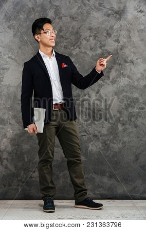 Full length portrait of a happy young asian man dressed in suit pointing finger away at copy space while holding laptop computer over gray background