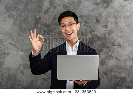 Portrait of a smiling young asian man dressed in suit holding laptop computer and showing ok gesture over gray background