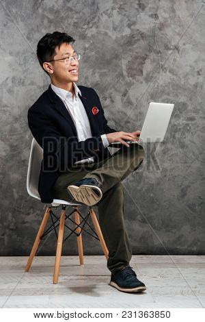 Full length portrait of a happy young asian man dressed in suit sitting in a chair and using laptop computer over gray background