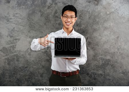 Portrait of a confident young asian man dressed in shirt pointing finger at blank screen laptop computer over gray background