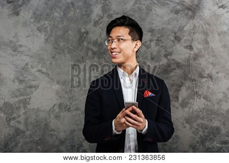 Portrait of a happy young asian man dressed in suit holding mobile phone and looking away over gray background