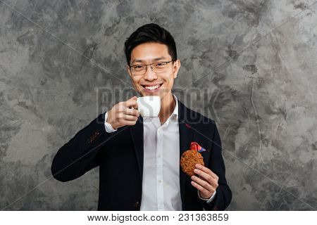 Portrait of a smiling young asian man dressed in suit drinking coffee with a cookie over gray background