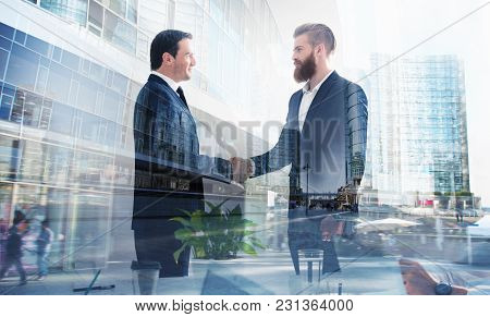Handshaking Business Person In The Office. Concept Of Teamwork And Business Partnership. Double Expo