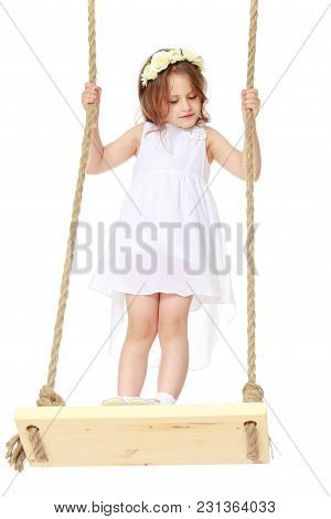 A Little Girl Is Swinging On A Rope Swing. The Concept Of A Happy Childhood, Summer Holidays, Playin