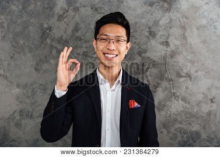Portrait of a cheerful young asian man dressed in suit showing ok gesture over gray background