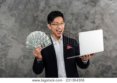 Portrait of a happy young asian man dressed in suit holding bunch of money banknotes while looking at laptop computer screen over gray background