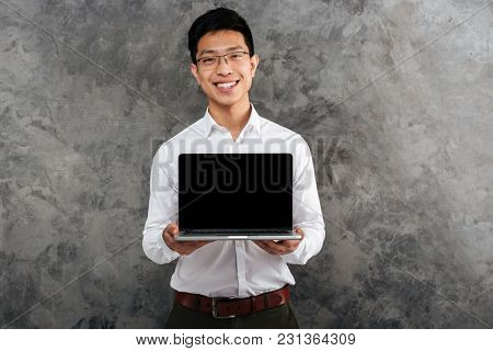 Portrait of a smiling young asian man dressed in shirt showing blank screen laptop computer over gray background