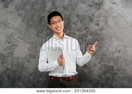 Portrait of a smiling young asian man dressed in shirt holding laptop computer and pointing finger away at copy space over gray background