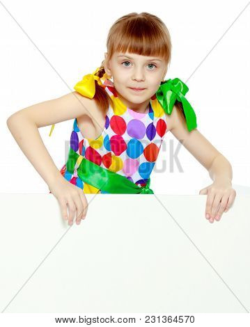 A Beautiful Caucasian Little Blonde Girl With Long Pigtails, In Which Large Colored Bows Are Braided