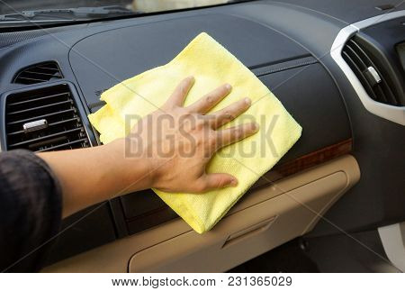 Hand Using A Microfiber Cloth To Clean The Inside Of A Car