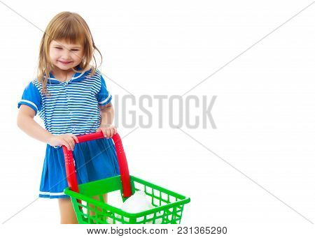 A Cute Little Girl With A Cart At The Supermarket Is Shopping. The Concept Of Advertising And Sellin
