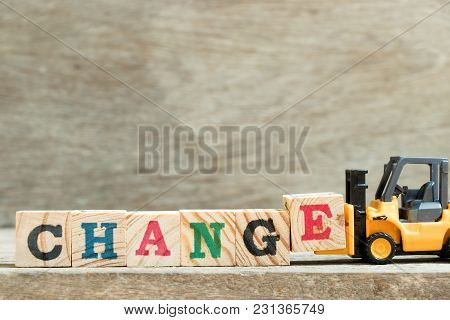 Toy Yellow Forklift Hold Block Letter E To Complete Word Change On Wood Background