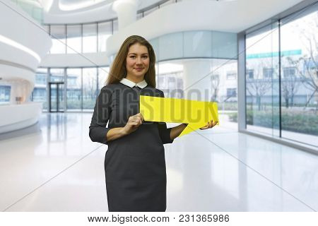 The Smiling Young Woman In Business Dress Holding A Yellow Plate In Hand On A Light Office Backgroun