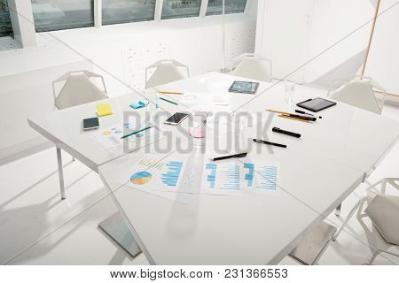 Table Reading For Business Meeting With Company Statistics And Reports