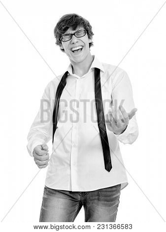 Young hispanic man wearing black glasses, white unbuttoned shirt, slim jeans and thin tie over his neck, playing imaginary guitar isolated on white background - fun and music concept, black and white