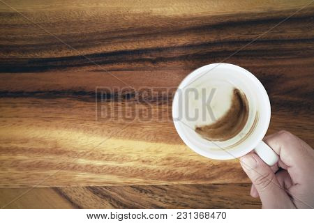 Hand Holding A Cup With Coffee Stain Cup On Wood Background, With Copy Space