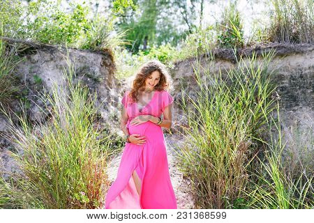 Happy And Proud Pregnant Woman Smiling Outdoors
