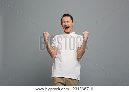 Image of excited young man standing isolated over grey wall background make winner gesture.