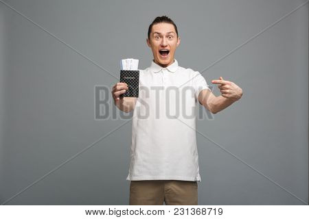 Photo of surprised young man standing isolated over grey wall background. Looking camera showing passport with tickets pointing.