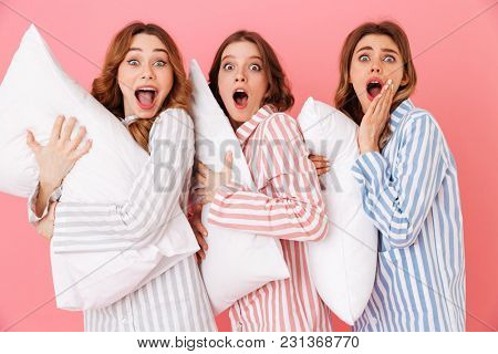 Image of female teenagegers 20s in home wear holding pillows and expressing excitement at slumber party isolated over pink background