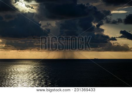 Ocean Landscape With Heavy Dark Clouds, Tanker Ship And Rain On Horizon