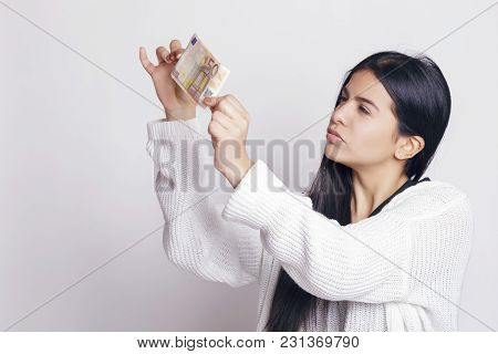 Latin Woman Checking A Fifty Euro Banknote.