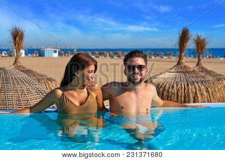 Tourist couple having bath in infinity pool on a beach resort in summer vacation
