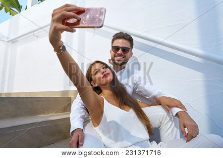 Young couple selfie photo with smarphone in a white stairway outdoor