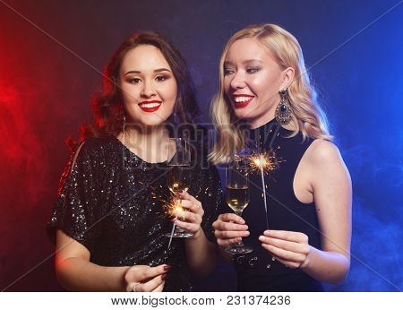 Party time. Two beautiful young women with wine glasses and spar