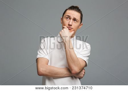 Photo of thoughtful young man standing isolated over grey wall background. Looking aside.