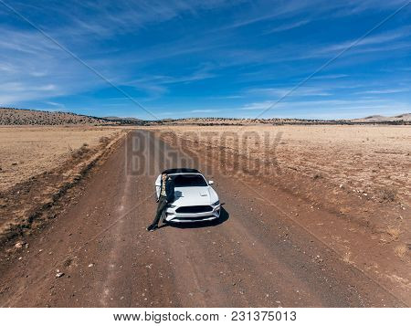 Man Traveling By Car On The Desert Road.