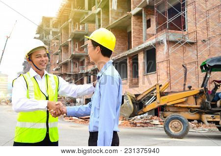 Asian Engineers Shake Hands At The Construction Site
