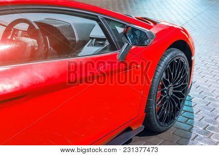 Front Wing And The Wheel Of The Car Are A Supercar, At Night In A Parking Lot In The City