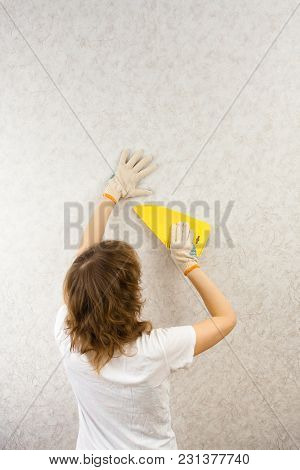 Woman Smoothing Wallpaper With Spatula On The Wall