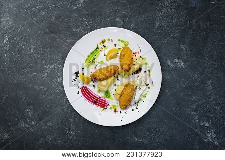 Fish Cutlets Stuffed With Quail Eggs With Mashed Potatoes, Served On The White Plate And On The Grey
