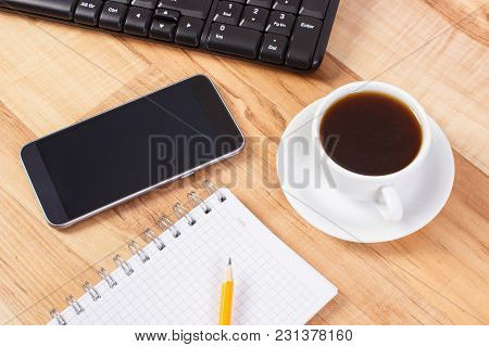Smart Phone With Notepad For Writing Notes And Cup Of Black Coffee On Table, Using Mobile Telephone
