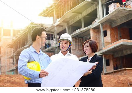 Asian Engineers Having Discussion At The Construction Site
