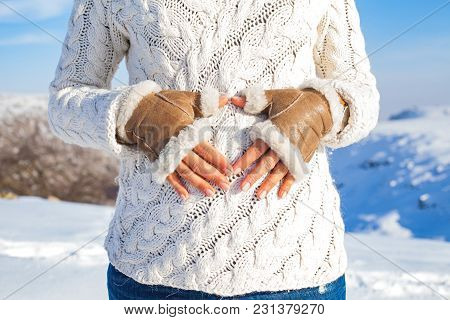 Close Up Woman Showing Heart Sigmn On Baby Bump On A Sunny Winter Day - Maternity Concept
