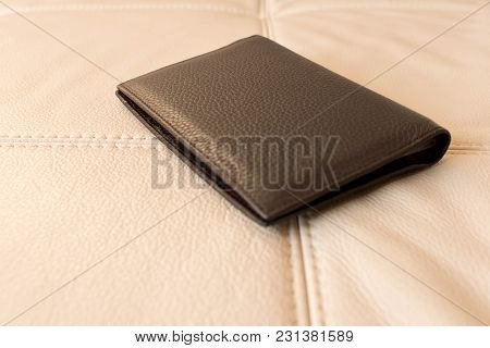Brown Leather Wallet On The Background Of The Beige Leather Couch .