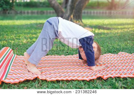 Cute Little Asian 18 Months / 1 Year Old Toddler Baby Boy Child Practices Yoga In Downward Facing Do