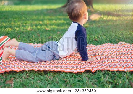Cute Little Asian 18 Months / 1 Year Old Toddler Baby Boy Child Practices Yoga In Cobra Pose And Med